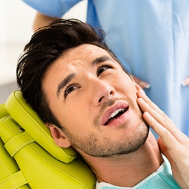 Man in dental chair holding his cheek