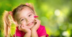 little girl smiling hands on face