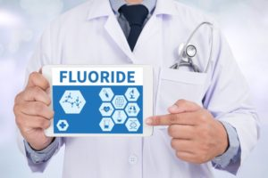 dentist holding sign with fluoride written